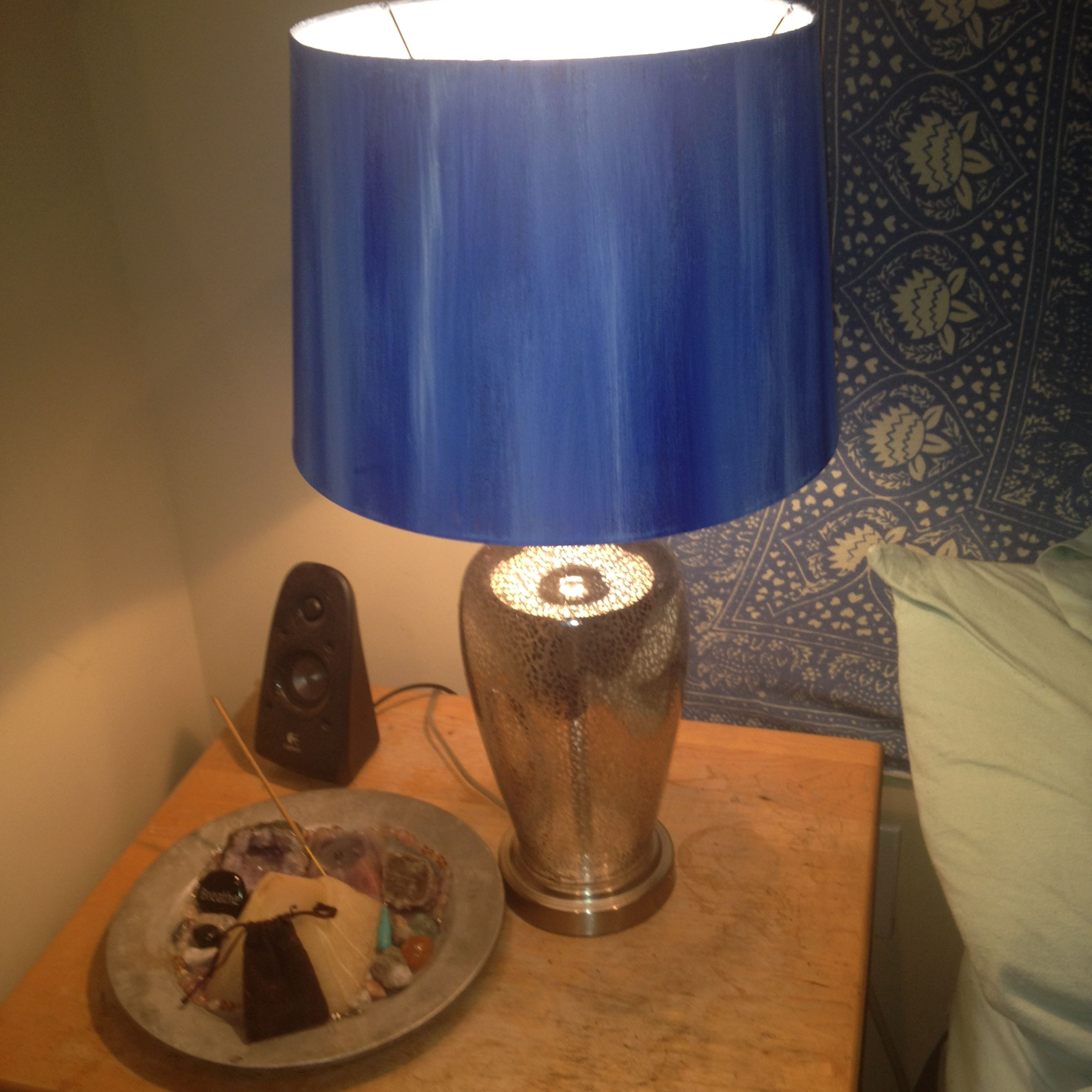 I was bored with the desk lamp I had next to my bed, so I found a cool lamp base, painted an old gross lampshade and voila! DIY success!  Simply thrift around, find a lamp you love with any fabric lampshade. Buy fabric paint (I only used blue and white and messed around with different shades to create a palate of my choice).  Get a paint brush.   I painted with strokes up and down with the dark blue in patches all around the lampshade, then gradually blended the other light blues and white…