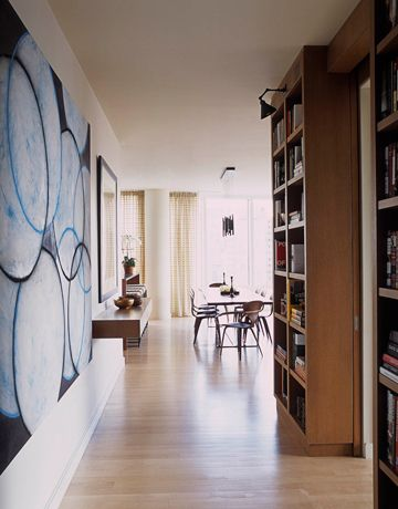 """Where other people see a bookcase light, Cohler sees a link to the past. Based on a model from the turn of the last century, """"that oil-can light is the design equivalent of comfort food."""" The painting in the entrance hall is by Mark Humphrey.   - HouseBeautiful.com"""