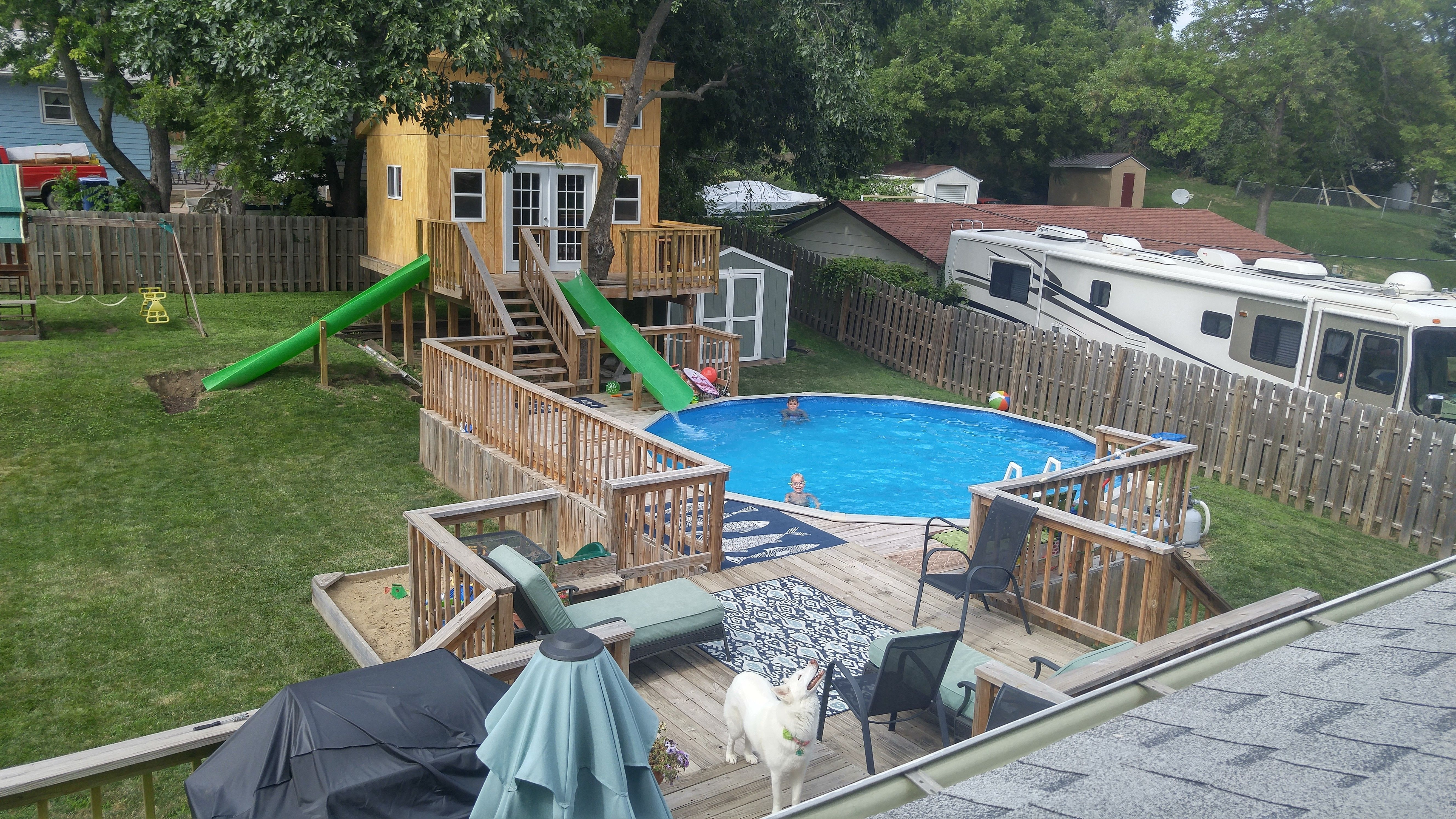 Backyard tree house with above ground pool water slide for Above ground pool house ideas