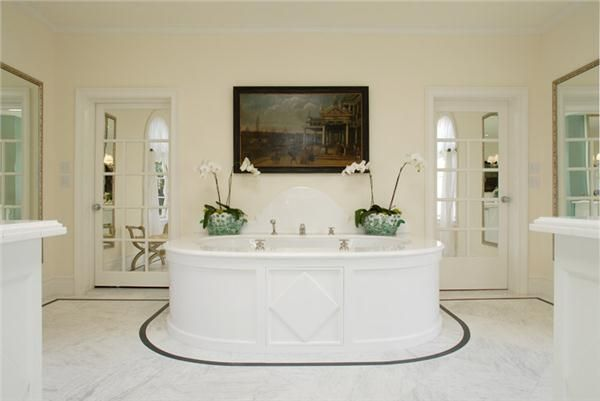 For those who appreciate symmetry, a curvaceous tub creates a focal point in the bathroom. Flooring details outline and add drama to the look. @timothycorrigan