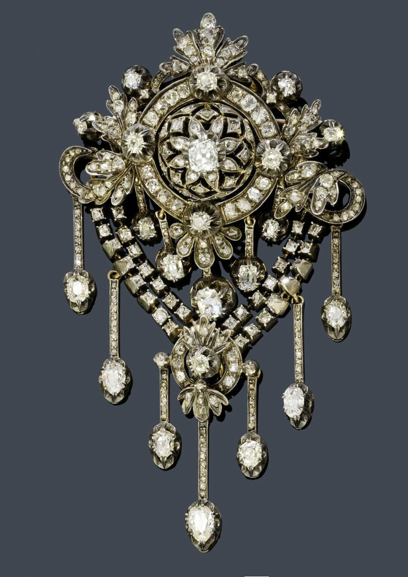 DIAMOND BROOCH, ca. 1880.   Silver over pink gold.   Fancy, florally open-worked brooch with circle, bow, palmette and leaf motifs, and 5 pendants with old European cut diamonds as the lower part. Below, a double garland with a palmette motif and 7 flexibly mounted, diamond-set pendants. With a total of 22 old European cut diamonds weighing ca. 3.50 ct and numerous old European cut diamonds and rose-cut diamonds weighing ca. 2.80 ct. Ca. 9.5 cm.