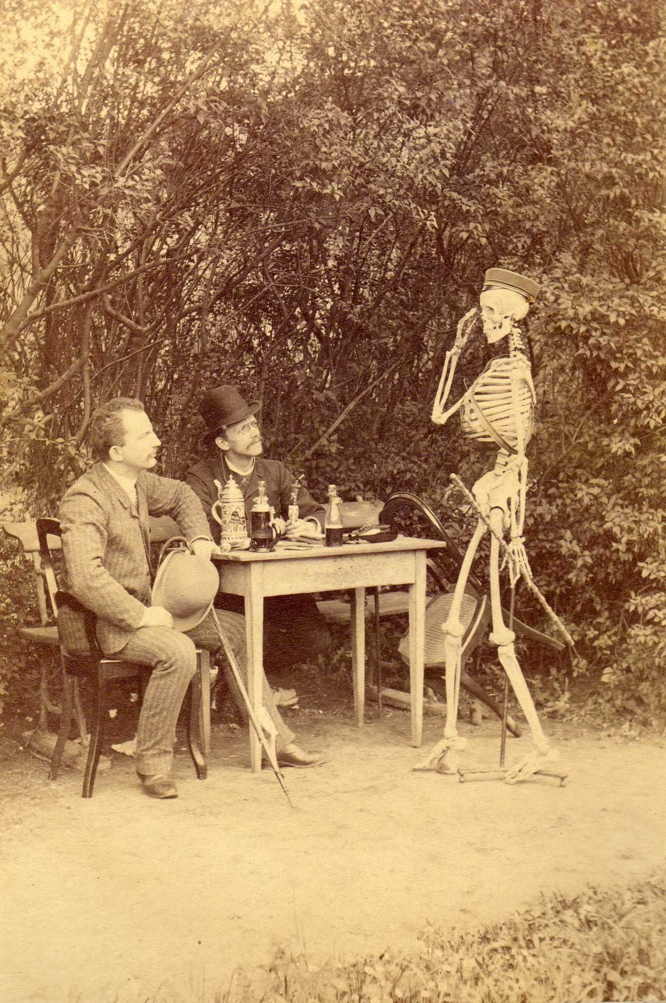"German students, about 1890, posing with a skeleton wearing a student's cap. The picture is titled ""der Skatspiel mit freund Hein"" - a game of cards with Death."