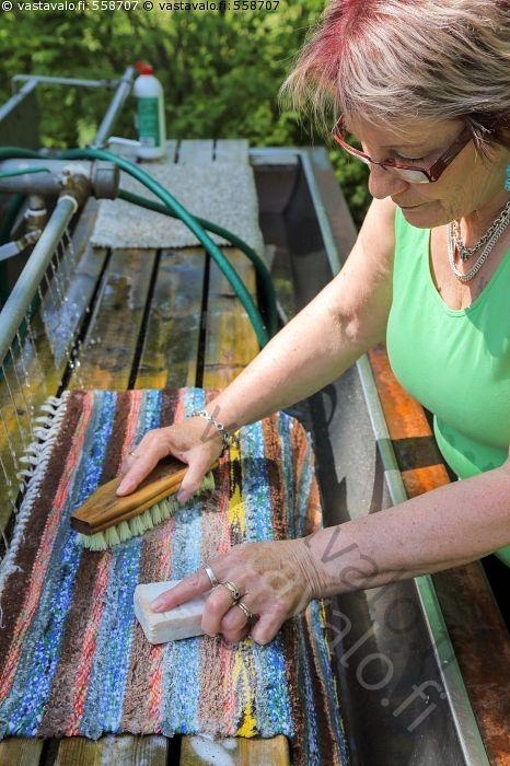 Mattopyykillä - matto matonpesu matonpesupaikka mattopyykki räsymatto pesu puhdistus puhdistaa pestä juuriharja harja käsinpesu pesuaine pesuvaahto vesi valua vesipesu käsi kädet nainen Kouvola