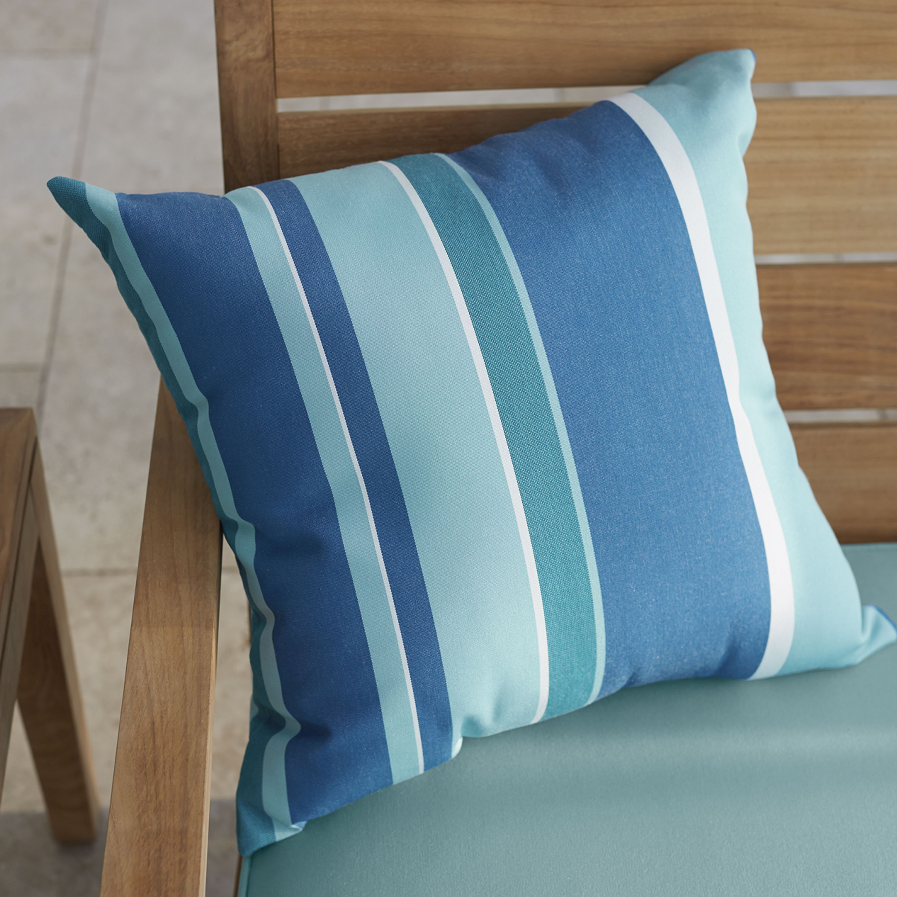 Thin and thick stripes of sea-inspired blues add a splash of color to the outdoor sofa or lounge chair. Made of Sunbrella acrylic, the pillow is weather- and fade-resistant.