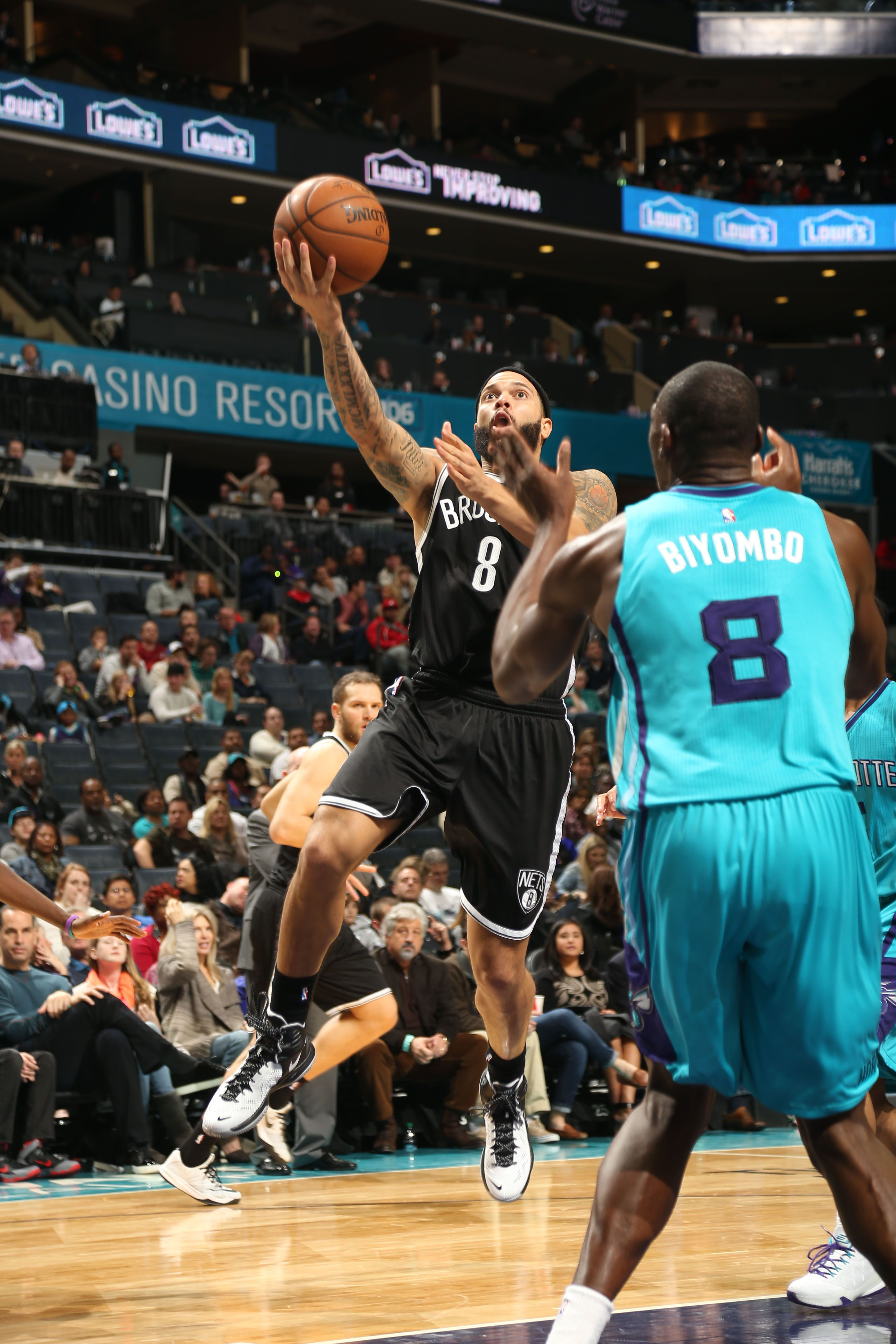 Deron Williams #8 of the Brooklyn Nets goes up for a shot against the Charlotte Hornets at the Time Warner Cable Arena on December 13, 2014 in Charlotte, North Carolina.