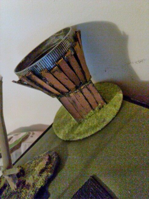 I made this easy sniper tower. A foam block glues to a cd to start. Nailed a large peanut butter lid to it. Snipped popsicle sticks for planks on base and top then glued to outside. Slapped some brown and silver paint on. Finished with grass flock on bottom and attached a strand of rope so models can climb it.