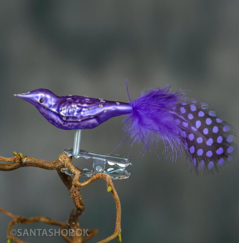 Når julepynten skal være en fugl til juletræet.Lilla fantasifugl i mundblæst glas med hale i fjer. Glasfuglen er malet med mat lilla farve og dekoreret med prikker i sølvglimmer. Øjet er sort og næbet malet med sølvglimmer. Halen er lavet i li
