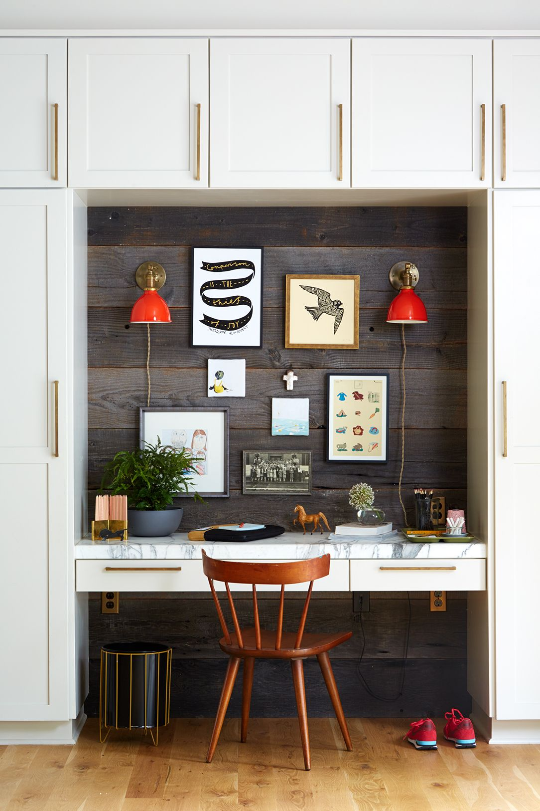 Dark wood home office with red wall sconces, small gallery wall, and white cabinetry