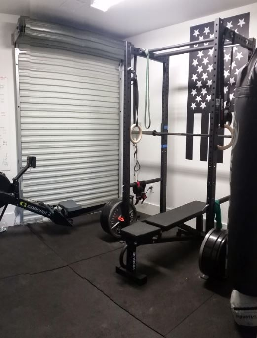 We like this garage gym with a tall roll up door home gym gym