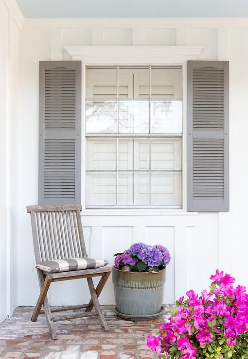 Beautiful white home exterior walls frame a window finished with ...