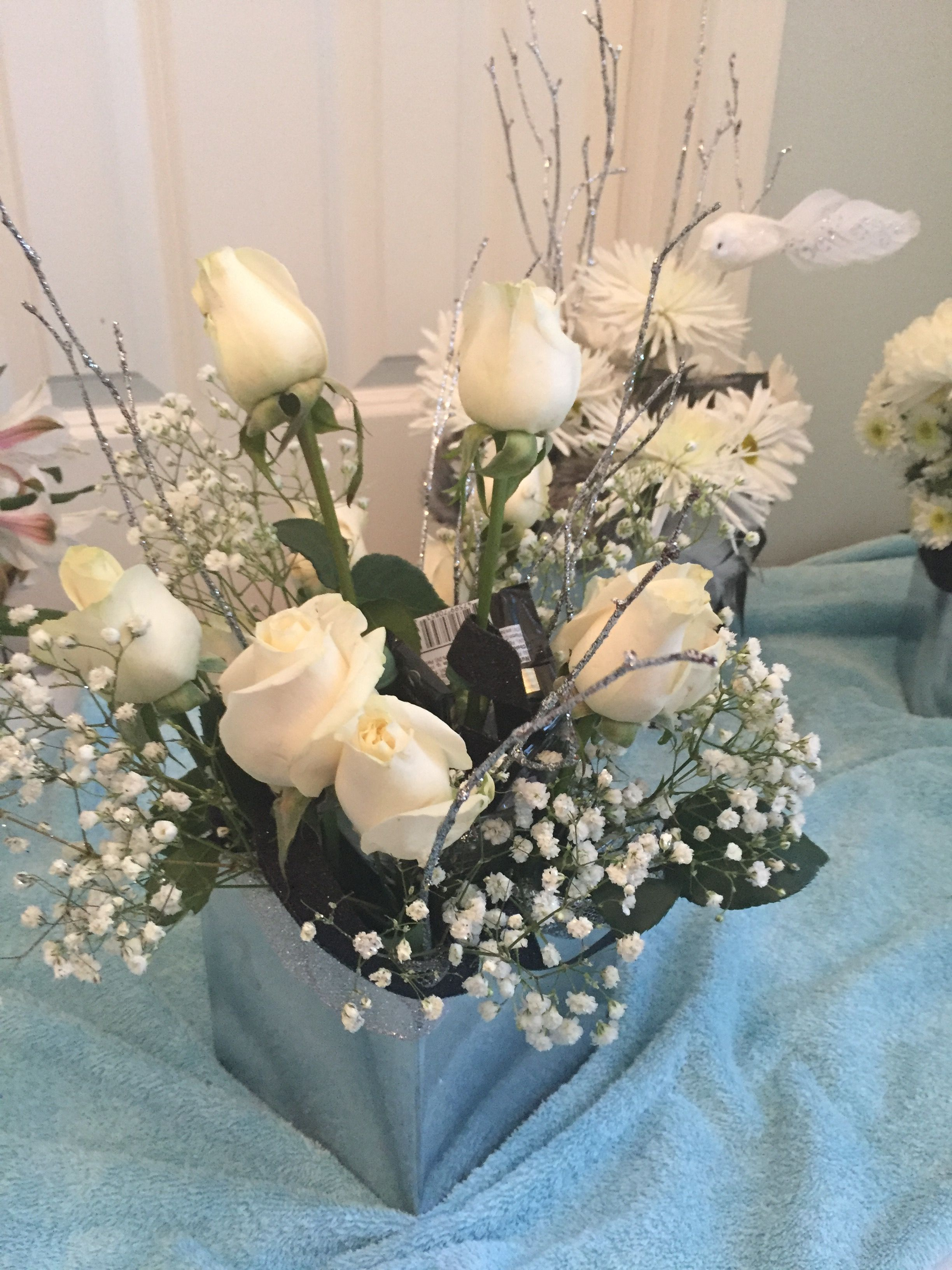 Daiquiri glass with rhinestones and chocolate surrounded by white roses baby's breath and branches,