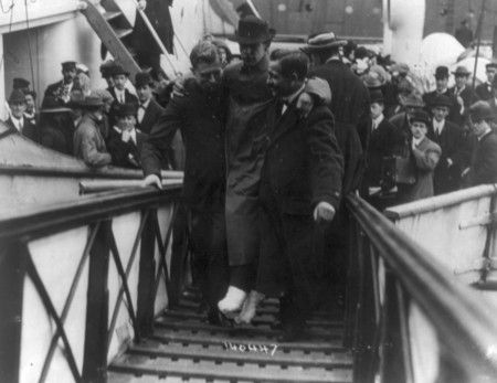 Description: Black and white photograph of Harold Bride, a survivor of the Titanic tragedy. Harold was a wireless operator of the Titanic. Here you can see that his feet are bandaged and he is being carried up ramp of ship, 1912.