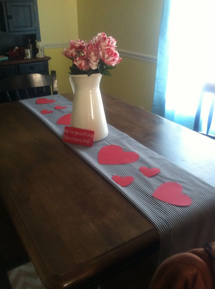 This is an Alice in wonderland inspired table decor. A black and white piece of fabric folded as the table runner. 3 bouquets of white roses from the dollar store painted red. A vinyl sign made on the cricut explore.