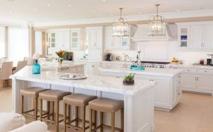 A big sized beach style kitchen with an all-white furnitures.