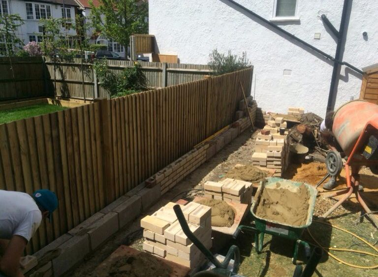 9 rear garden wall in buff bricks with planters decking and patio under construction - Brick Garden 2015