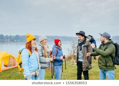 Embark on an adventure Happy five best friends getting ready for travel Man and woman argue where to go Beautiful lake on background Friendship trip travel destination co...