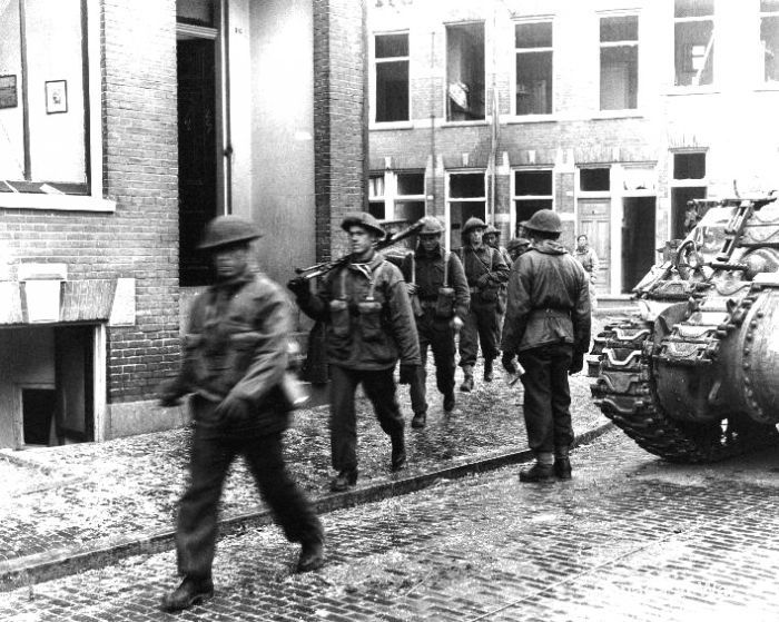 Soldiers of the Perth Regiment move through Arnhem, April 15th 1945. Governor General's Horse Guards' Sherman to the right.