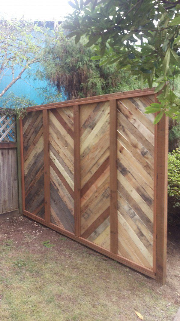 Backyard fence made with repurposed pallets pallet for Repurposed pallet projects