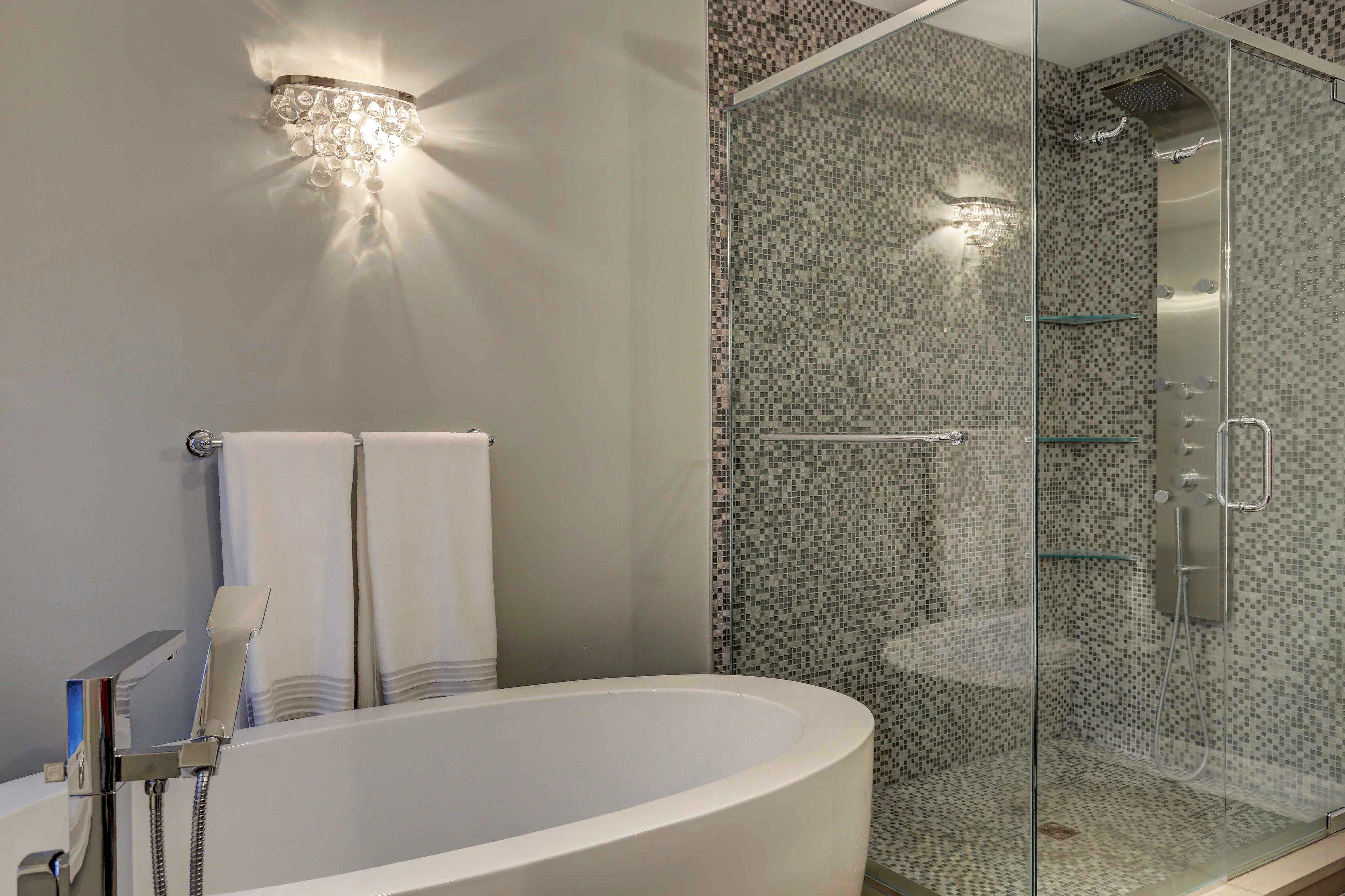 Elegant spa bathroom with modern soaking tub and walk-in shower with ...