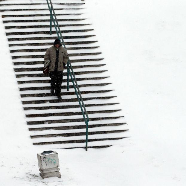 Un uomo su una scala coperta di neve a Belgrado