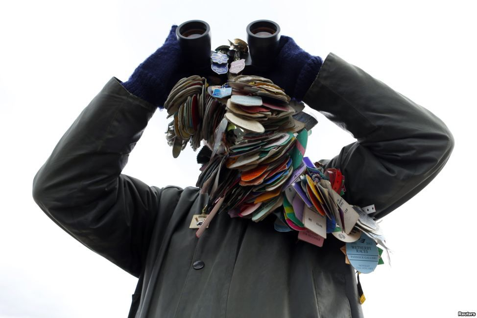 A racegoer, with all his previous race badges, with his binoculars during the Cheltenham Festival horse racing meet in Gloucestershire, western England