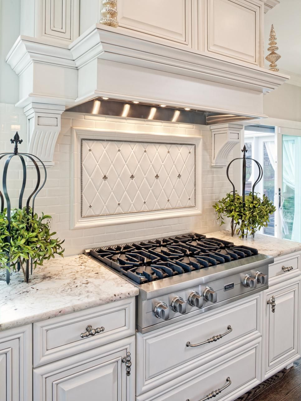 Light gray and silver accents and a white tile backsplash add