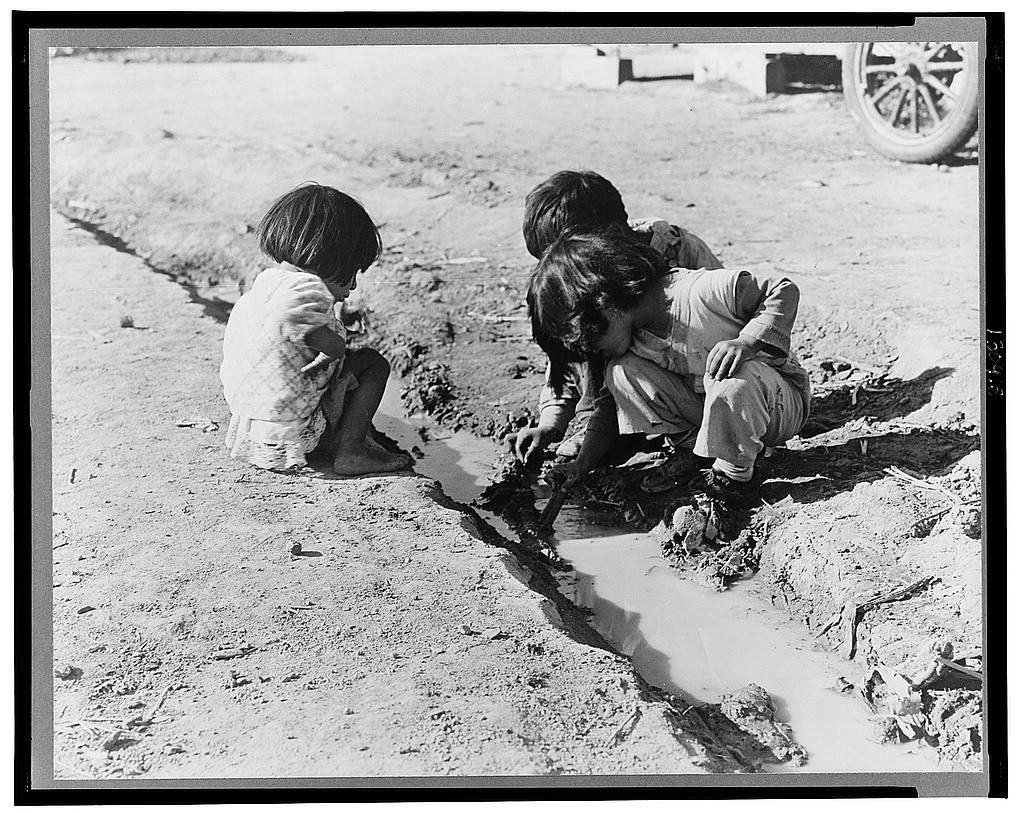 Mexican children playing in ditch which runs through