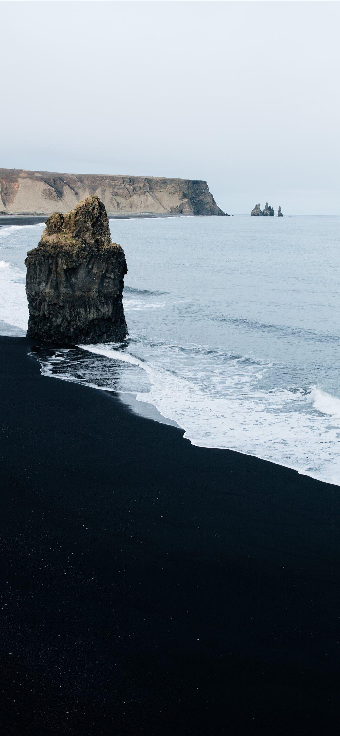 brown monolith rock on seashore iPhone 11 Wallpapers in