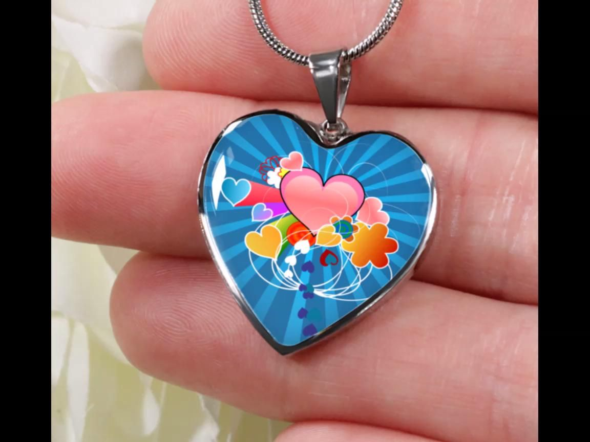 Rays of love are streaming out from a collection of colored hearts against a blue background on this exquisite design quality pendant. On a bangle or necklace. Low allergy Stainless Steel and poured glass with engraving and an 18k gold finish upgrade available too.  This is not available elsewhere - Online Exclusive. Order now for delivery of a unique mothers day gift. #onlineexclusive #mothersday #mothersdaygift #bangle #necklace #jewelryset #18kgold #stainlesssteel #handmadejewelry #USmade
