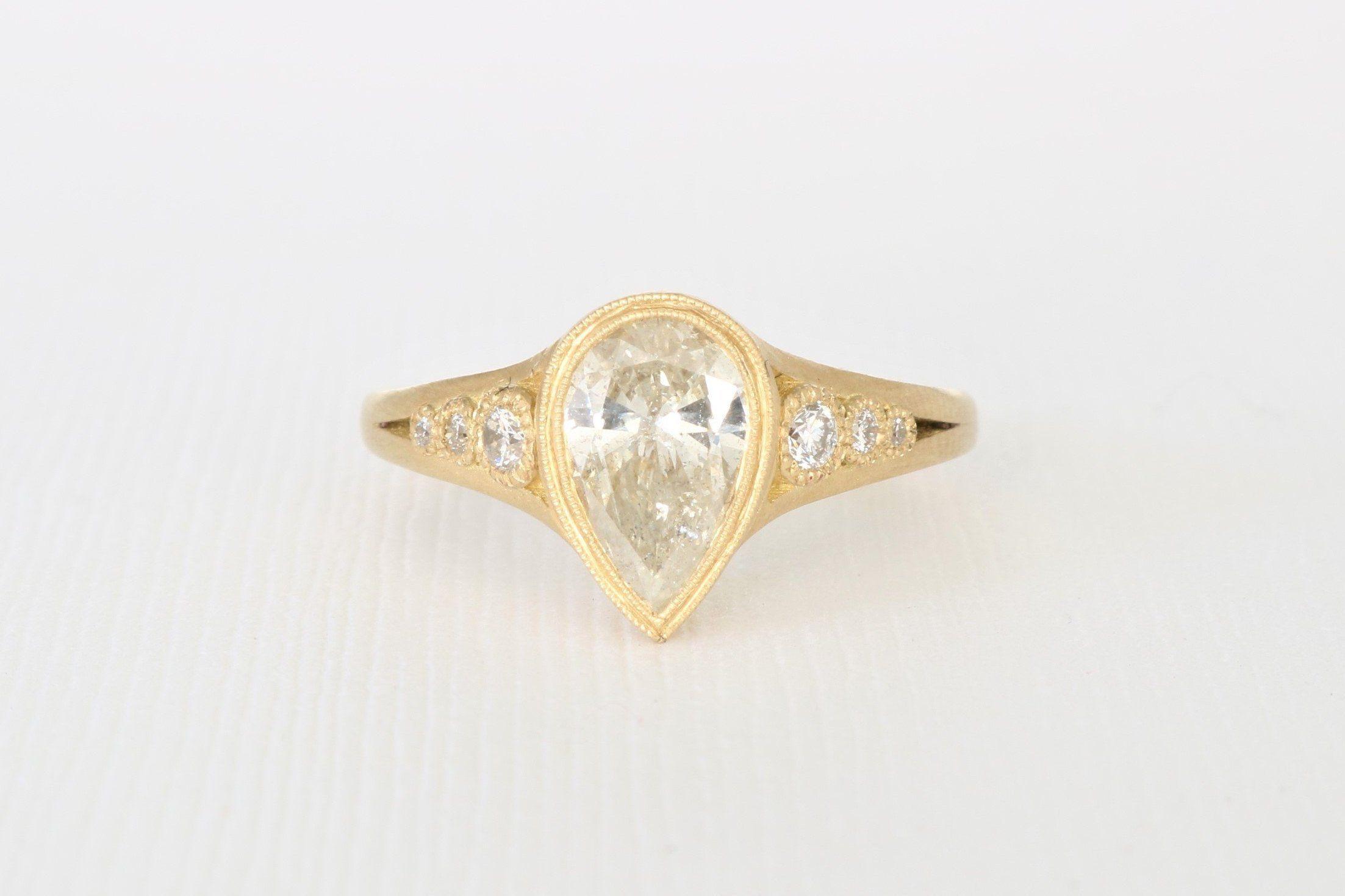 Hand milgrained pear cut diamond bezel ring in k yellow gold