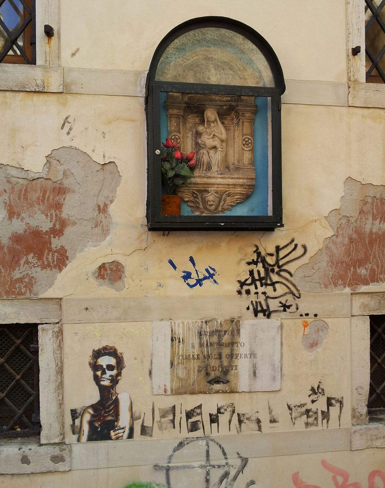 In Venice this graffiti of a skeletal junkie model is artfully posed beneath a madonna. From www.atthepinkhouse.tumblr.com