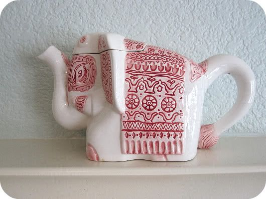White elephant teapot .... hung with red and white embroidered drapings, ceramic