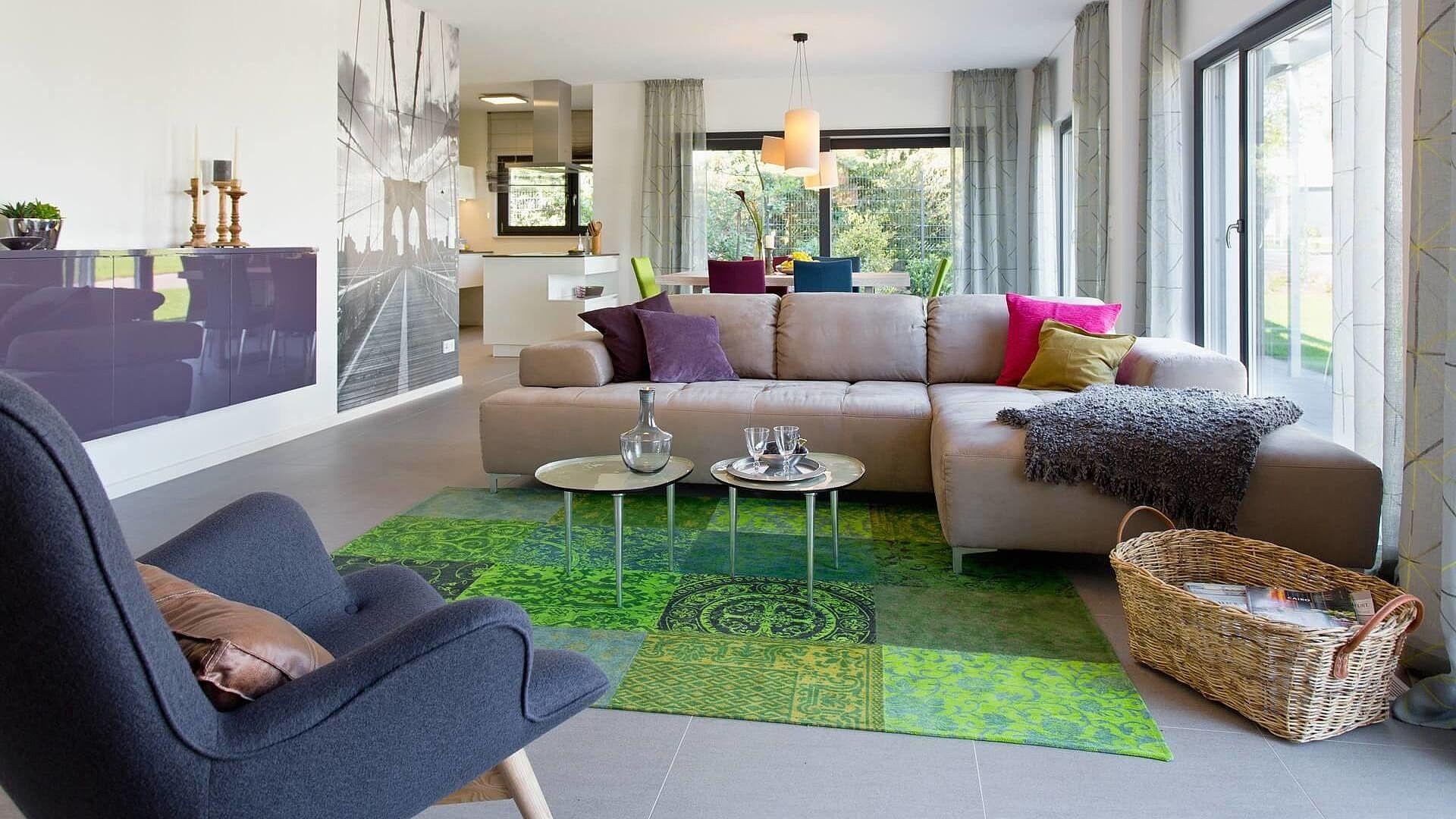 Wohnzimmer Helle Wande Bodentiefe Fenster Gruner Teppich Beige Couch Bunte Kissen Grauer Sessel Wandfoto