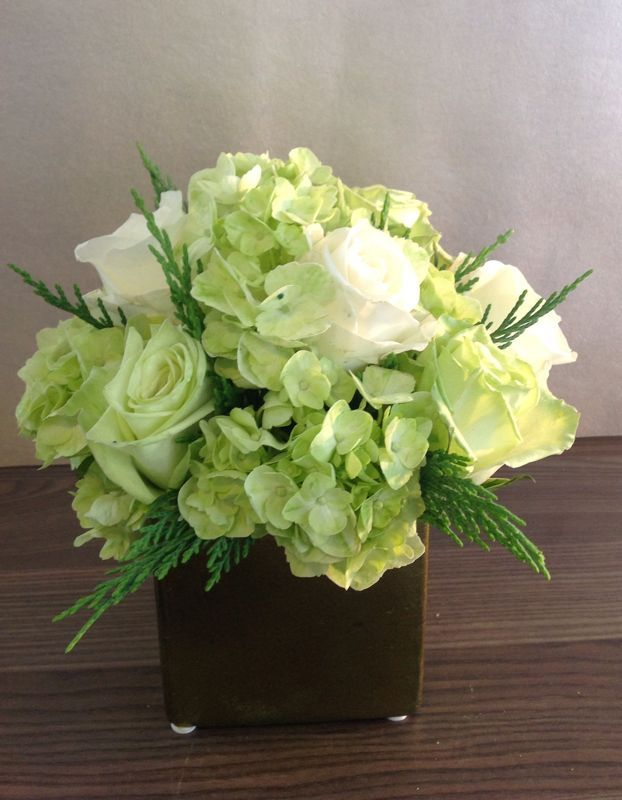 winter 1 Eden Floral Boutiques Holiday Collection! Green hydrangea with white roses and holiday green for. Holiday table centerpiece or gift. Square cube arrangements.