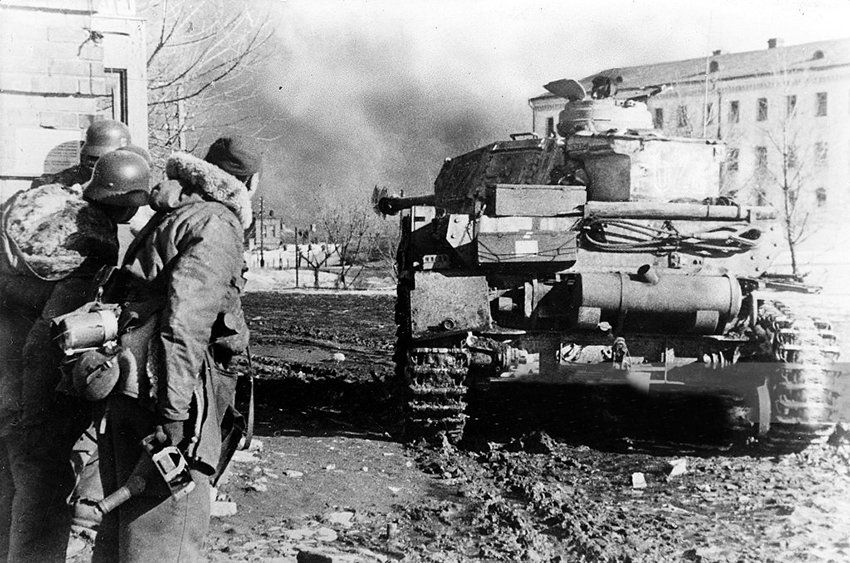 Panzergrenadiers look at a Panzerkampfwagen IV which aims at Russian troops in Kharkov, 1943.