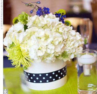Blue polka-dot ribbon wrapped around a vase finished off the white, blue, and green floral centerpieces.
