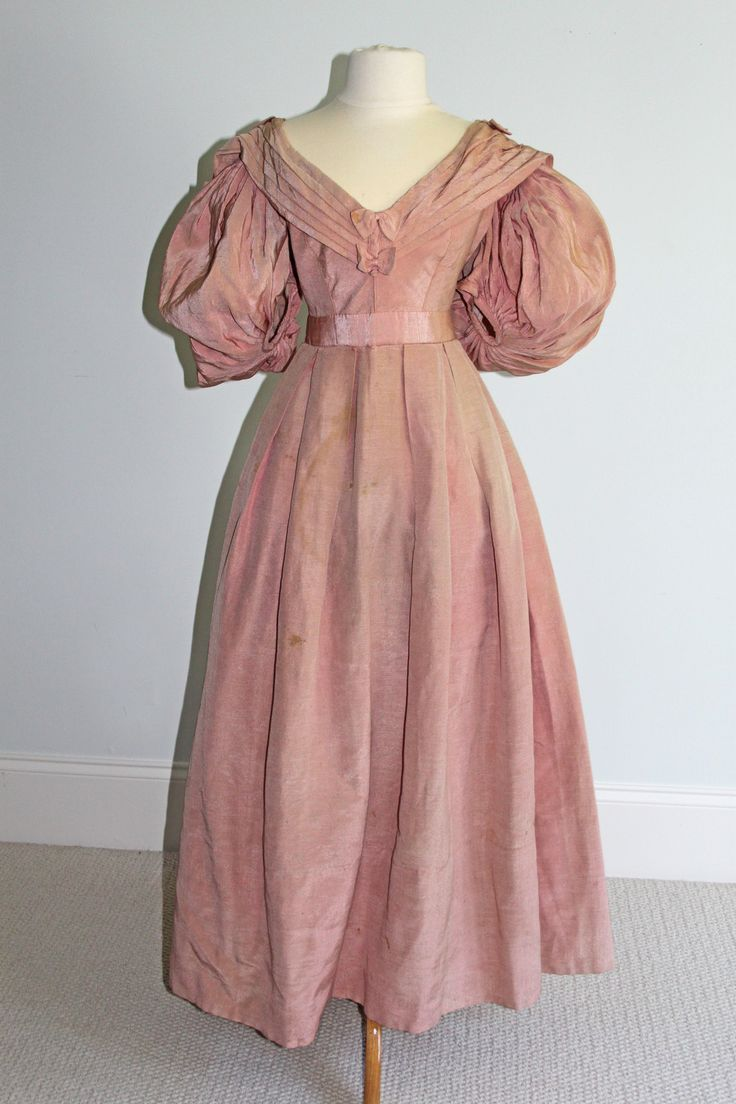 From the Seller  This is a very rare pink silk faille ball gown from the 1830s. Provenance England. From the Blogger: Sorry, dear seller, but this is not from the 1830's. The sleeve style is very indicative of the mid 1890's (1894-1898) and the machine sewing is a dead giveaway of a later date. The hooks and eyes are styled from the late Victorian/early Edwardian period. Also, I have yet to come across a Romantic era dress with a Bertha collar like that. #edwardianperiod