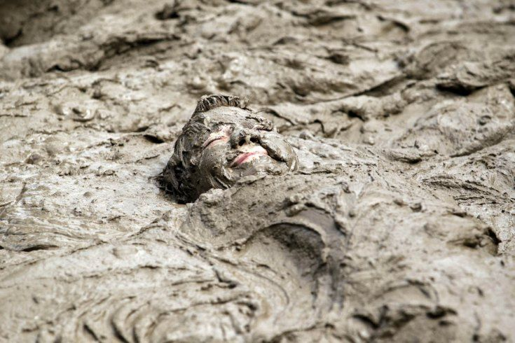 July 9, 2013. Zach Miller buries himself in the mud pit during the 26th annual Mud Day at Nankin Mills recreation complex in Westland, Mich.
