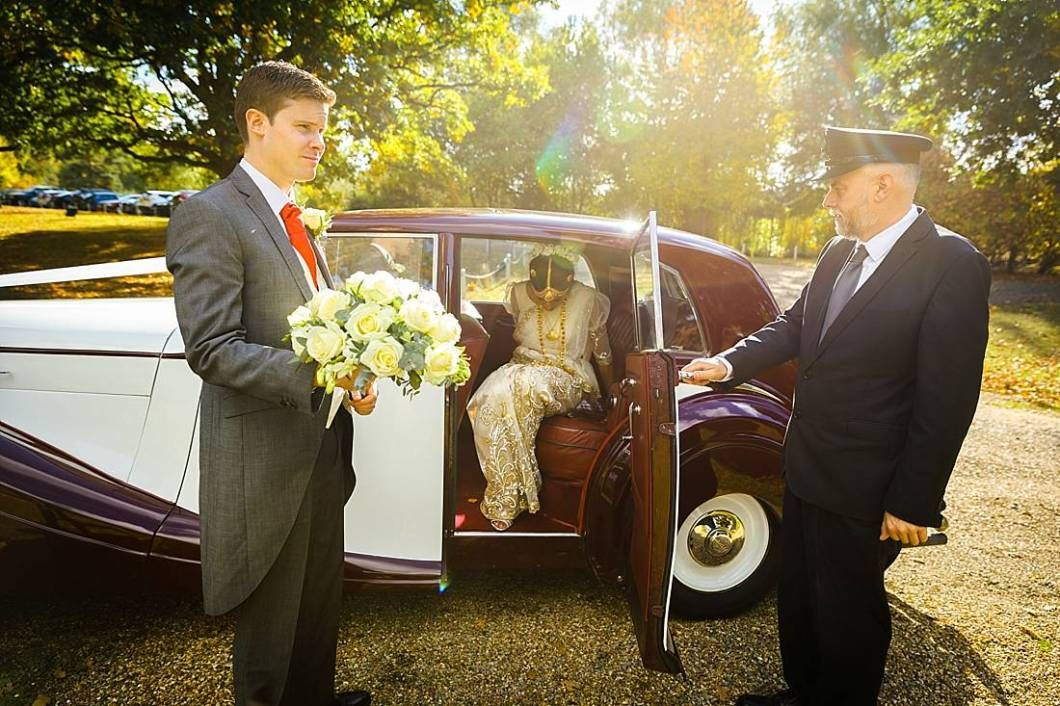 Bride getting out of vintage car at Braxted Park