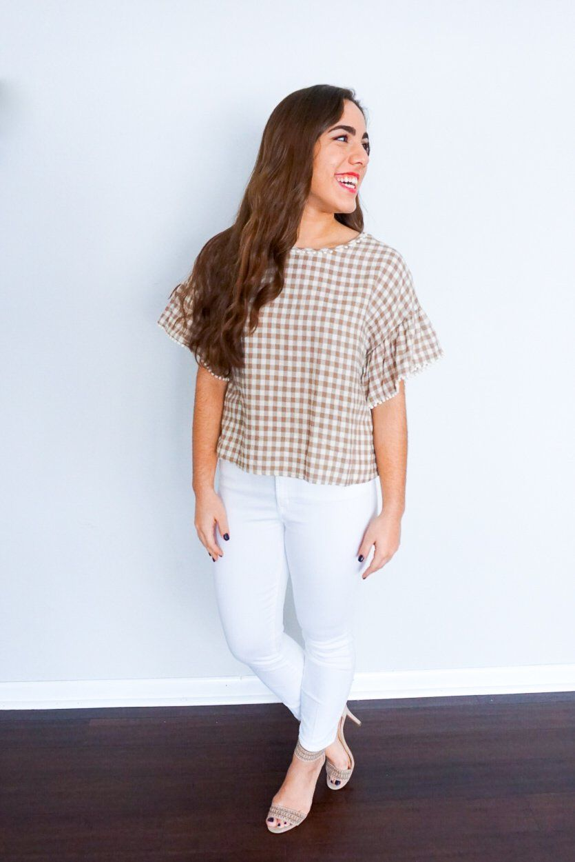 3dded8812b07b6 Everything about this shirt is absolutely adorable. From the tan and white  gingham print to the ruffle sleeves with the small pom pom details to the  twisted ...