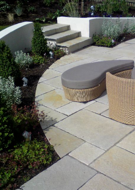 Curved rendered wall and limestone patio split level for Curved garden wall designs