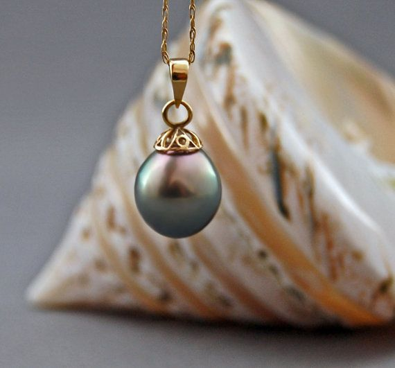Gorgeous, large 13.5mm x 12mm hard to find silver gray with peacock Tahitian pearl pendant set in solid 14kt yellow gold - not plated. The Stats: AAA grade Tahitian pearl; on the larger end of the size range - 13.5mm x 12mm; slightly baroque in shape; a beautiful, glowing, natural untreated silver gray color; smooth silky skin; silky high luster; rose with a bit of pistachio overtones and a subtle peacock iridescence. Flawless. Difficult to find color. 23mm or about 7/8 of an inch in…
