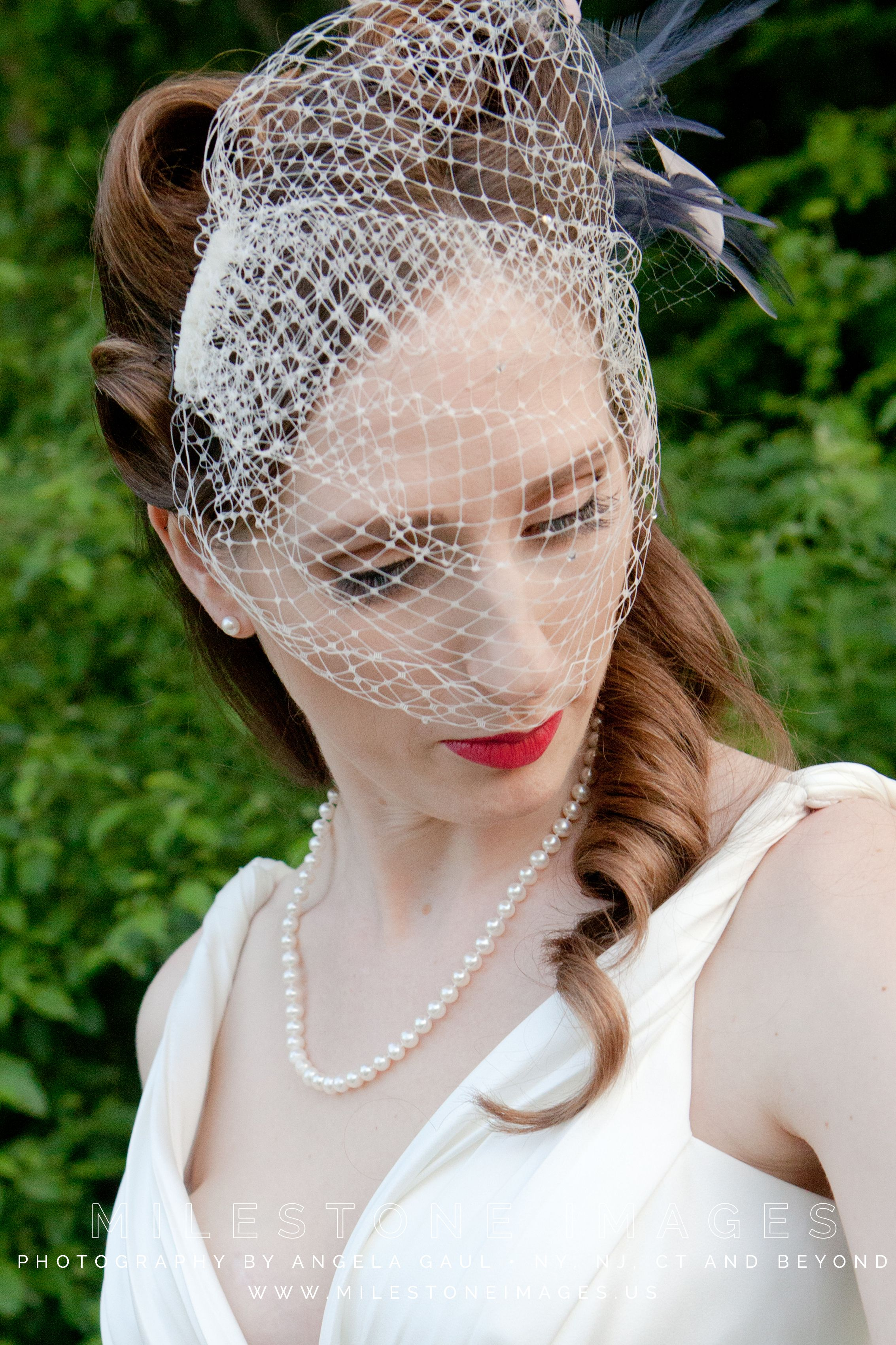 half undo with long curls and victory rolls, feather fascinator