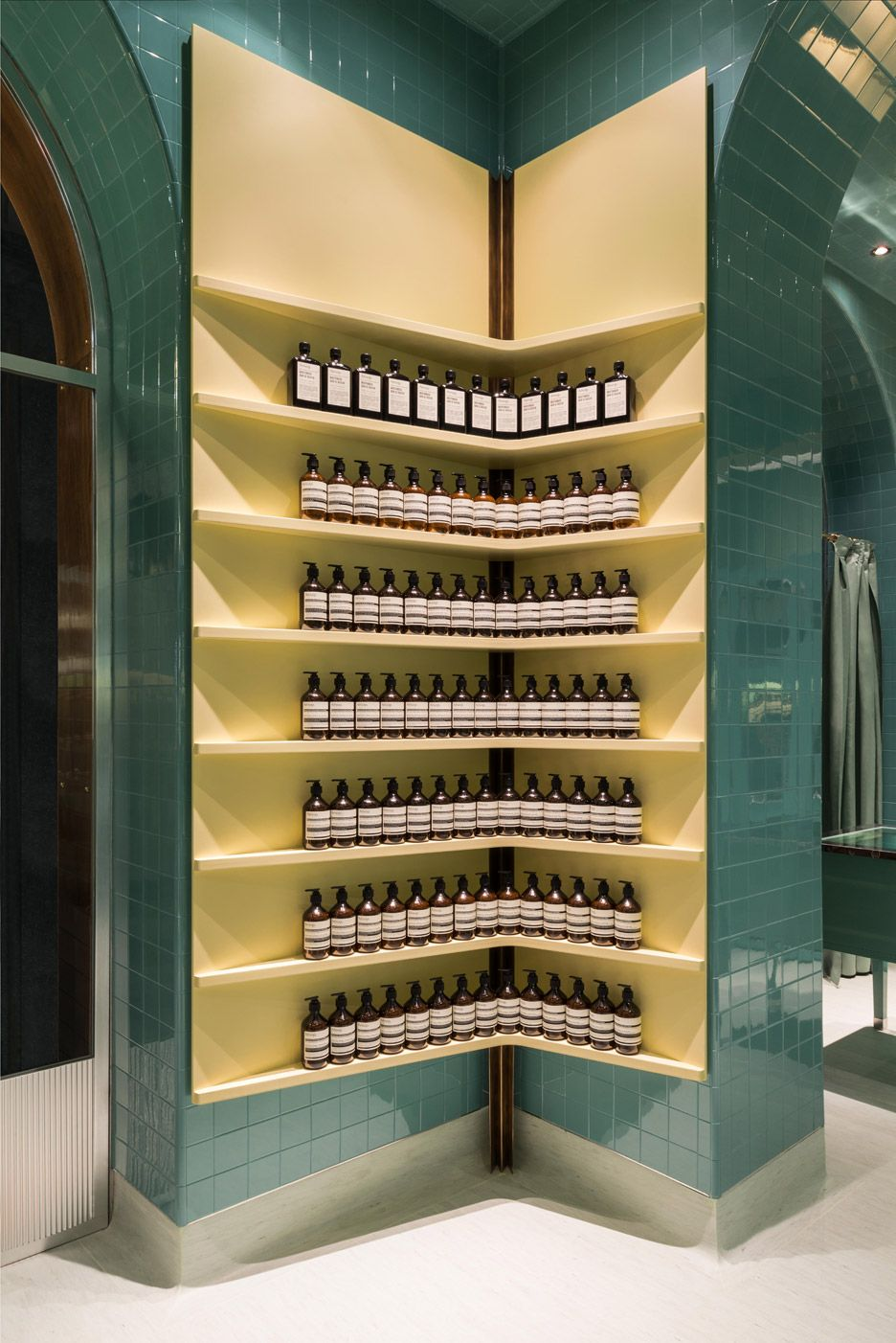 Green-coloured subway tiles are paired with lemon-yellow shelving inside skincare brand Aesop's second Milan branch