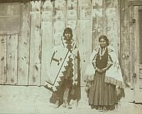 Navajo man and woman wearing rugs and standing in front of Warren Trading Post Co