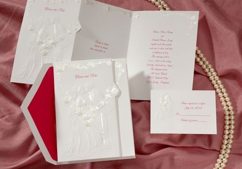 Love sealed with a kiss! This romantic wedding invitations with a loving couple is featured amid a heart-shaped wreath of pearl colored roses.