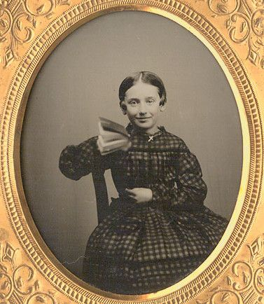 ca. 1858, ambrotype portrait of a smiling young girl with a book