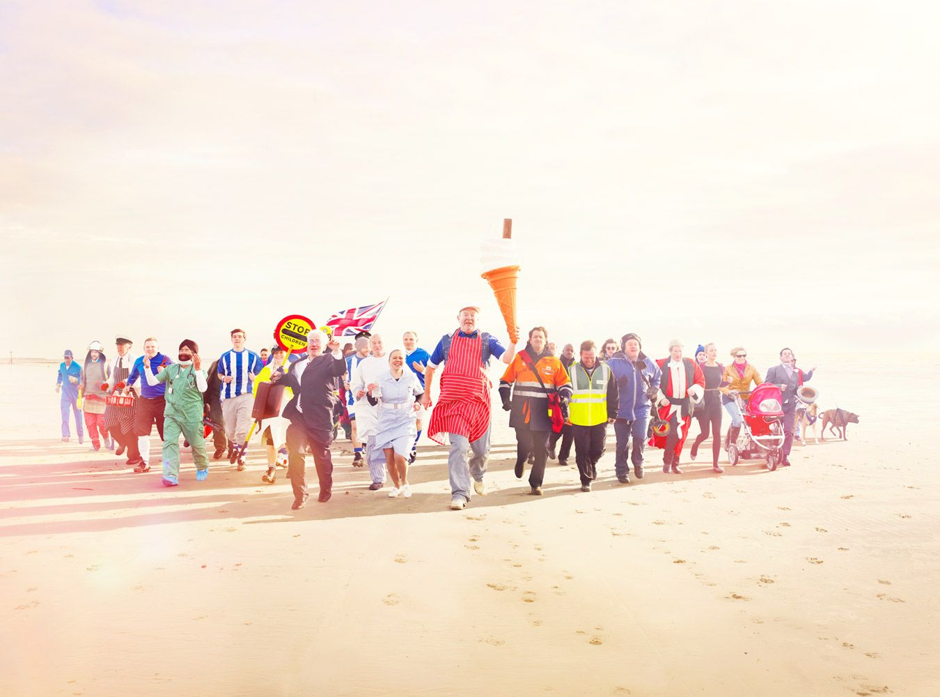 Oli Kellett Image - London Advertising Photographer - The Sun Newspaper Advertising Campaign - with people from all walks of life running together at the beach.