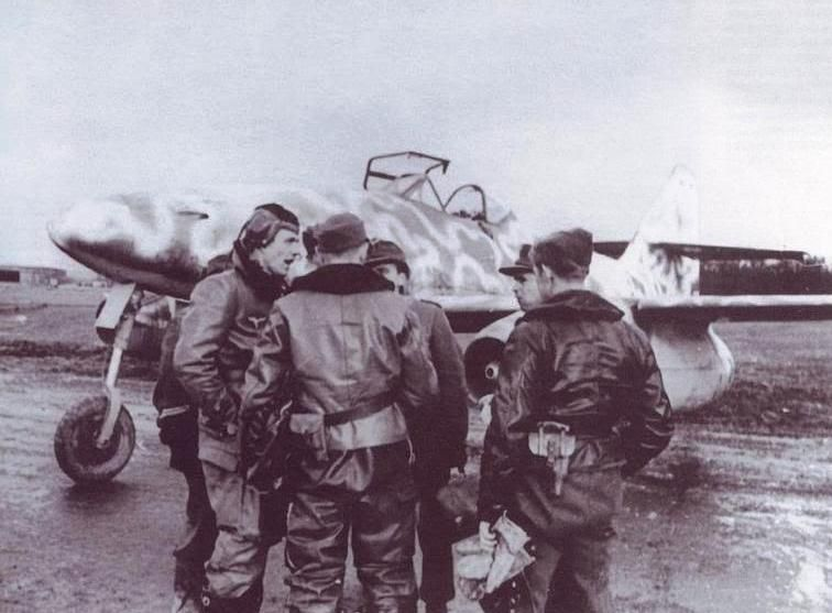 Pilots and Mechanics of 7./KG{J} 54 in front of one of their Me 262 A-1a coded B3+BH at Neuburg am Donau in early 1945.  Several aircraft of this unit had a RLM 76 wave pattern cammo sprayed over RLM 81 uppersurfaces in a random style applied over both national insignia and markings .