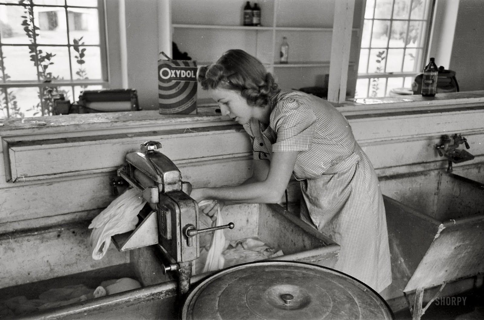 A woman hard at work doing the laundry with an old-fashioned ringer ...